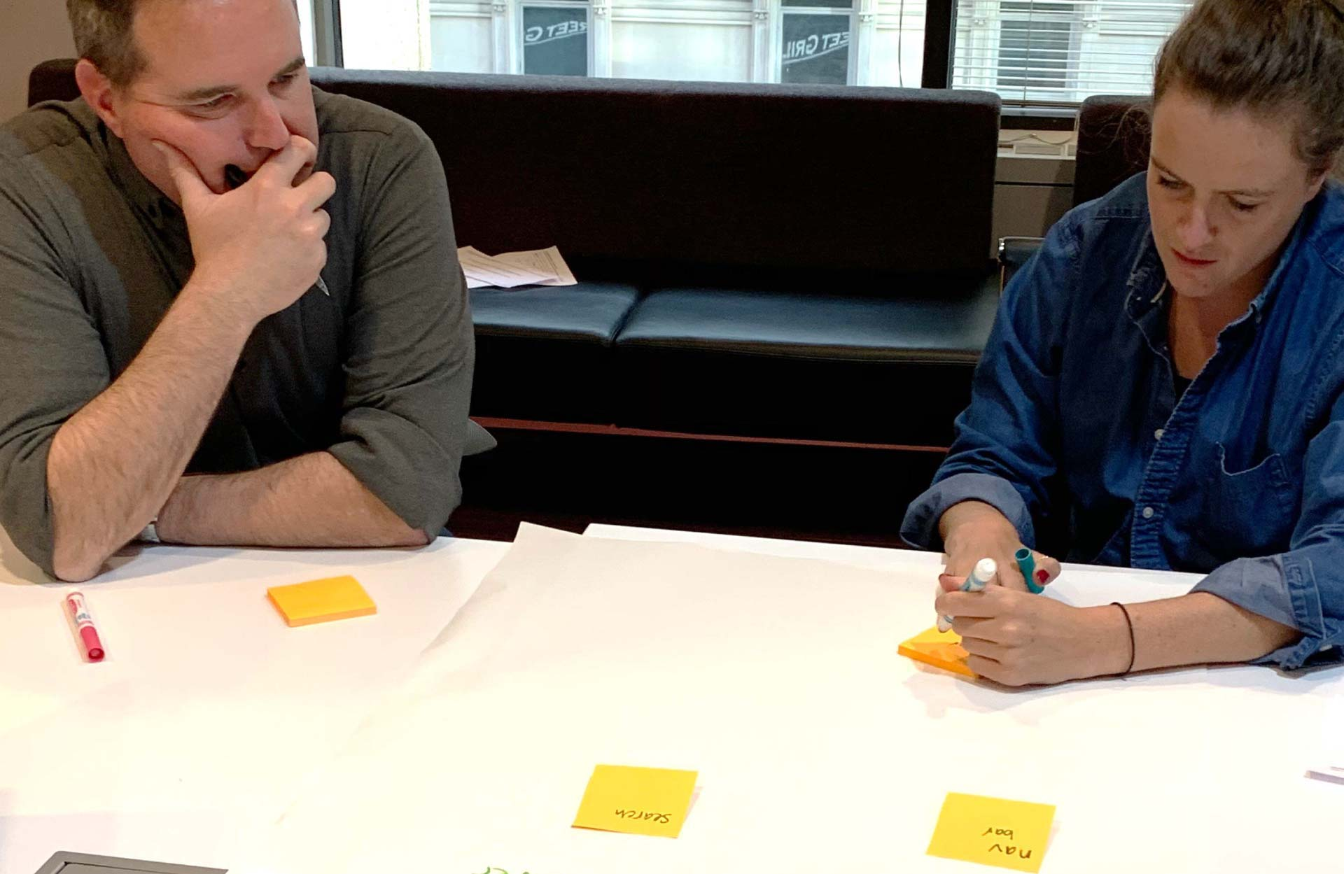 Two Industry Dive executives collaborating over sticky notes during the 'Elevator pitch descriptors' exercise.
