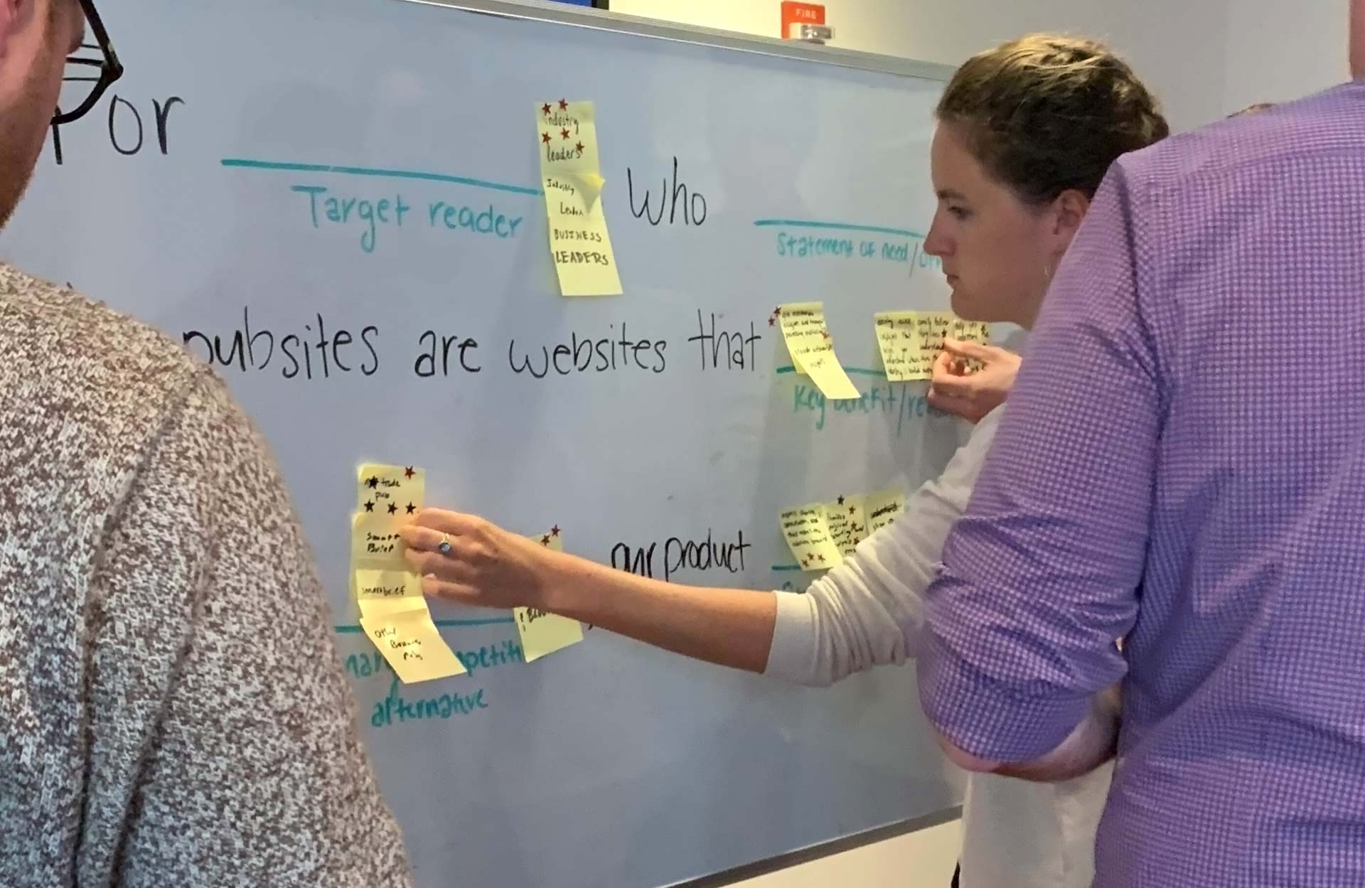 An Industry Dive executive posting a sticky note on a white board during the 'Working product vision statement' exercise.
